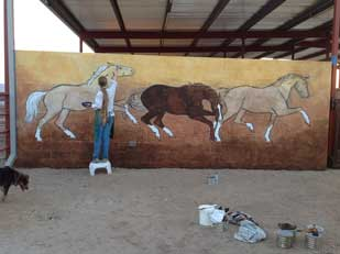 Ellen A. Cook painting in horses on wall