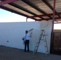 Ellen A. Cook putting color on the white wall